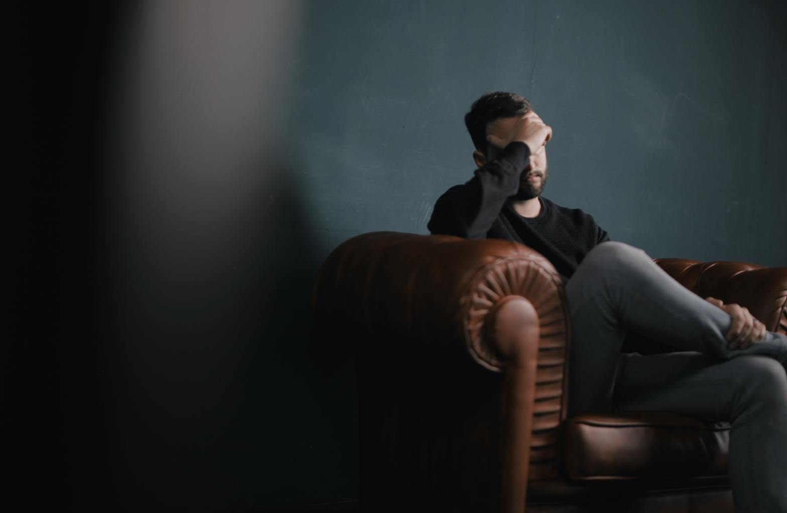 Man sitting with head in his hand