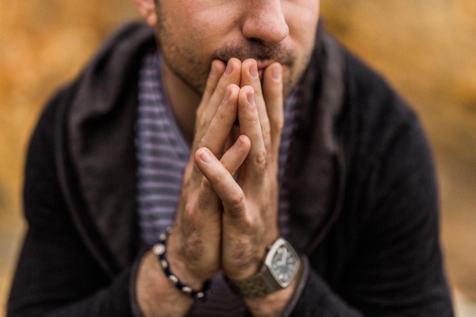 Man pressing his fingers to his lips worrying and overthinking