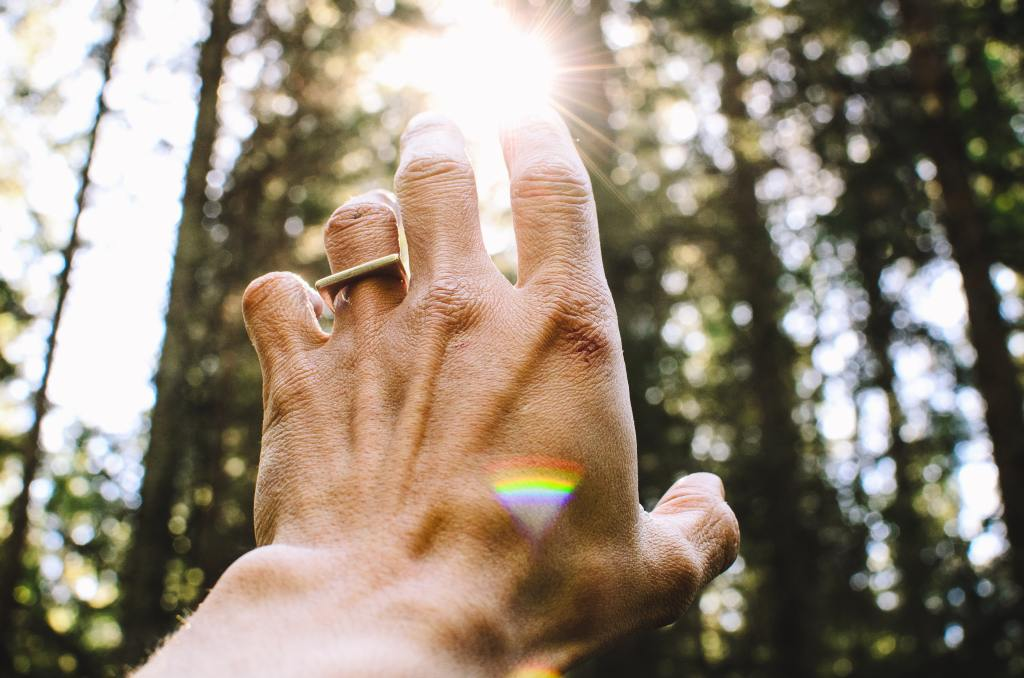 An outstretched hand reaches for the sun's energy. Reiki is a form of energy healing.