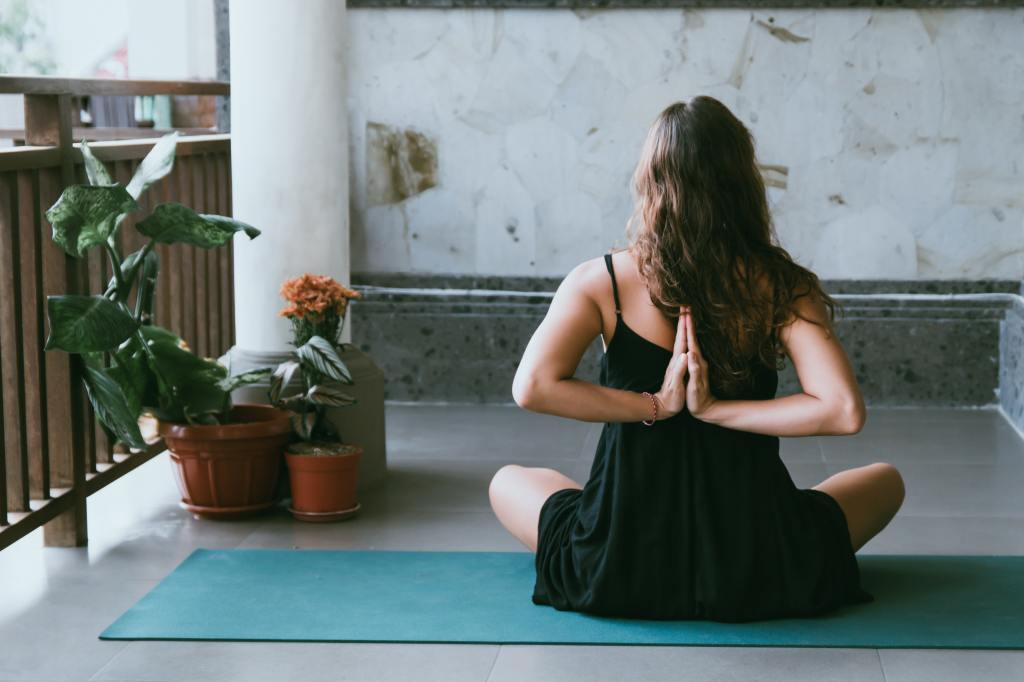 A woman in a yoga posture, calming her body, breath and mind.