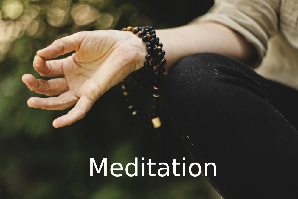 Meditation link, showing the hand of someone meditating with a mala.